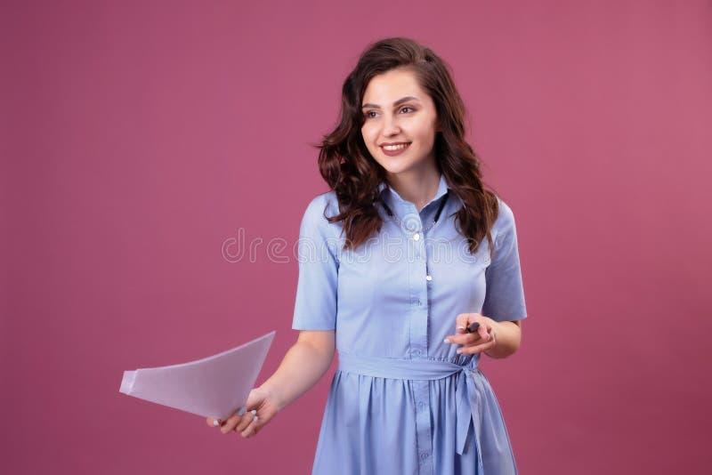 La mujer joven con los puntos a las hojas de papel, sostiene una pluma foto de archivo
