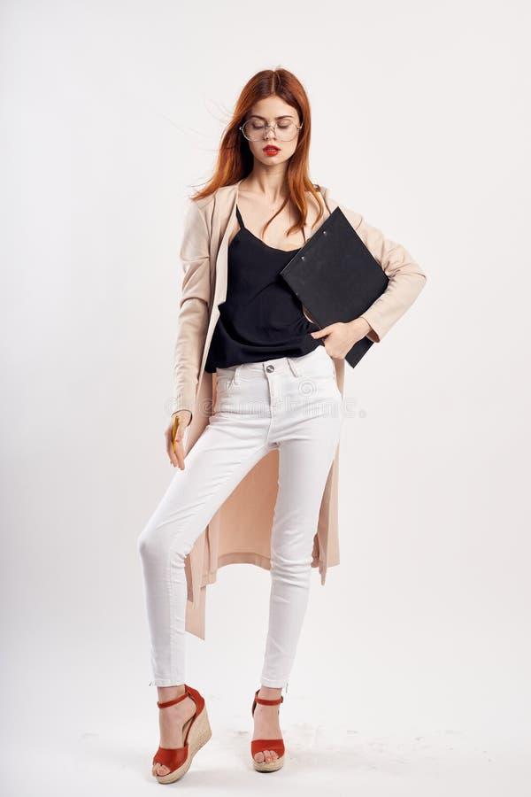 La mujer joven con los vidrios en un fondo ligero lleva a cabo documentos en el crecimiento completo, moda, estilo, belleza imagen de archivo libre de regalías