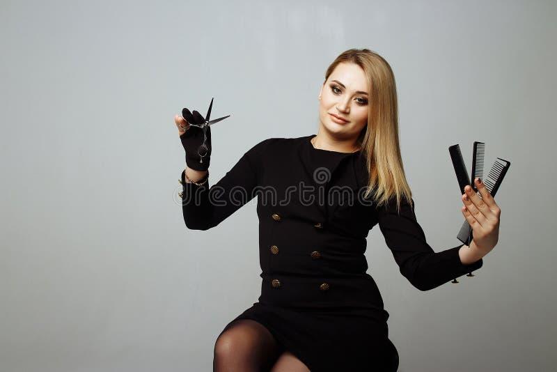 La mujer joven con mirada hermosa del pelo en las tijeras en un estudio de la mano tiró el fondo gris sostiene tres peines fotografía de archivo