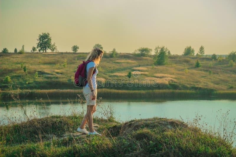 La mujer joven con la mochila rosada se está colocando en el cierre azul del fondo de las minas de la tiza para arriba en tiempo  imagenes de archivo