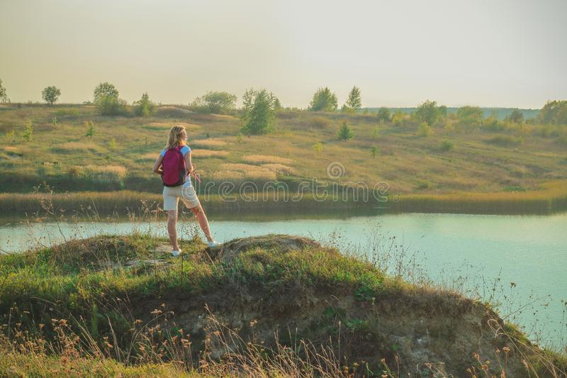 La mujer joven con la mochila rosada se está colocando en el cierre azul del fondo de las minas de la tiza para arriba en tiempo  fotos de archivo libres de regalías