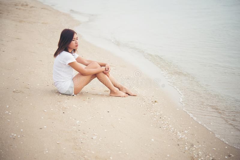 La mujer joven con la sensación sola de las miradas se sienta en la playa Mujer triste a imagenes de archivo