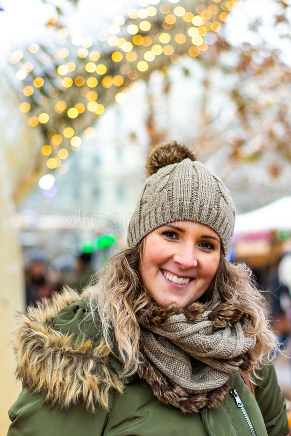 La mujer joven con la taza de té se está colocando antes de árbol de navidad en el invierno, mercado de la Navidad imagenes de archivo