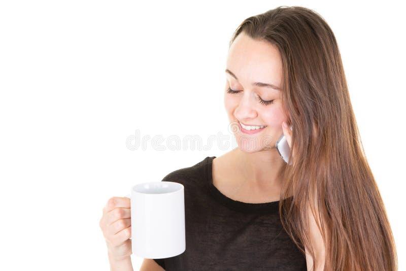 La mujer joven con la taza del t? del caf? tiene conversaci?n sobre el tel?fono elegante en el fondo blanco fotografía de archivo