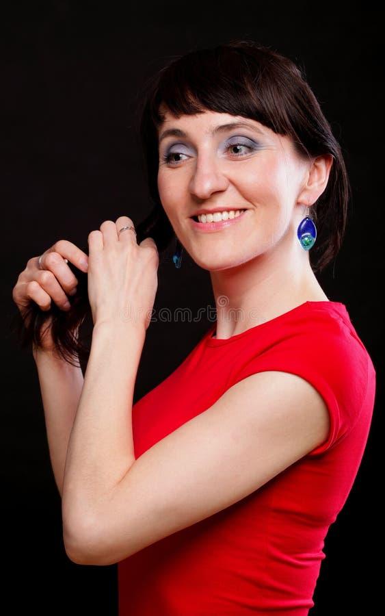 La mujer joven con una sonrisa muestra los pendientes foto de archivo libre de regalías