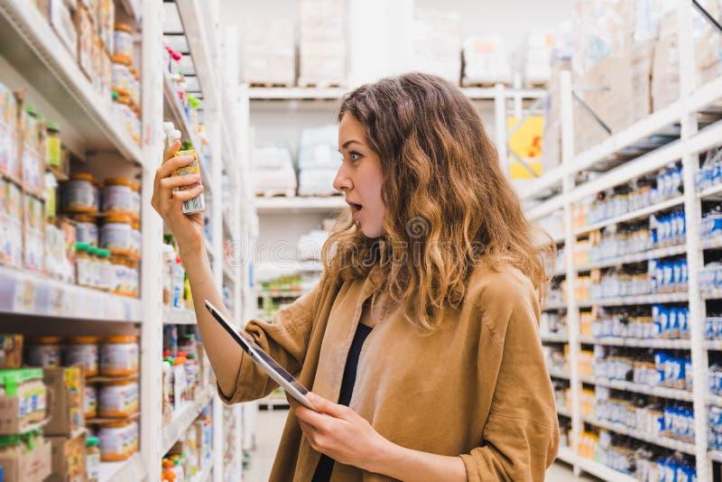 La mujer joven con una tableta en choque de la composición de los alimentos para niños en un supermercado, la muchacha lee emocio fotos de archivo libres de regalías