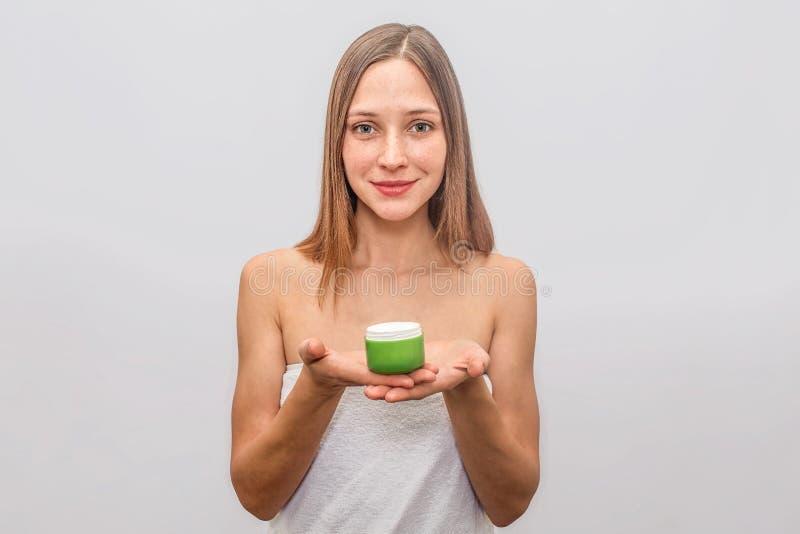 La mujer joven confiada y alegre coloca y sostiene el vidrio de nata con ambas manos Ella mira derecho la cámara Rubia foto de archivo libre de regalías