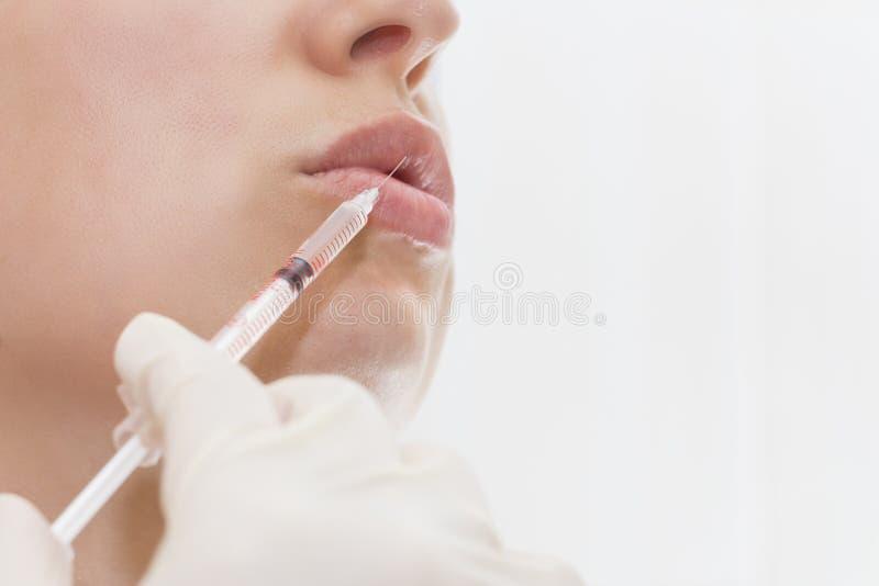 La mujer joven consigue la inyección del botox en sus labios Mujer en salón de belleza Clínica de la cirugía plástica fotografía de archivo