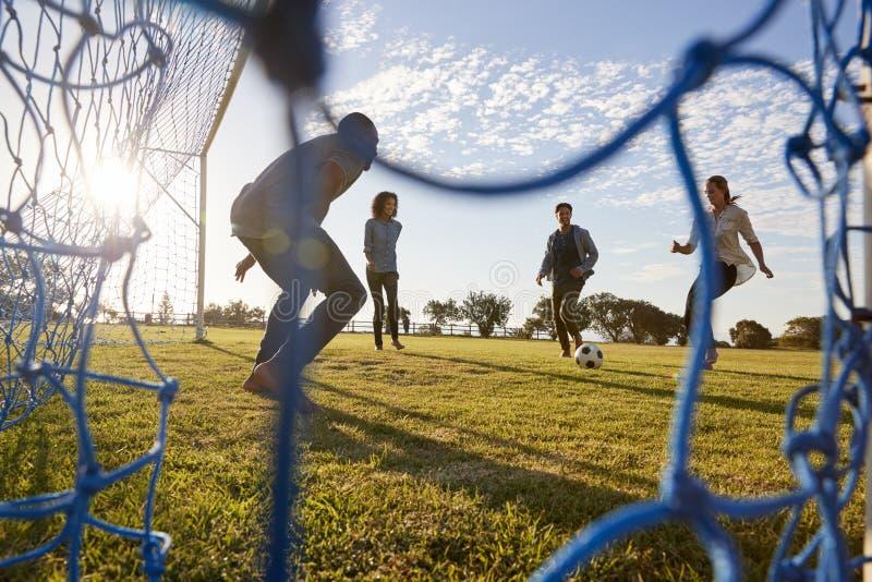 La mujer joven corre a un fútbol mientras que juega con los amigos fotos de archivo