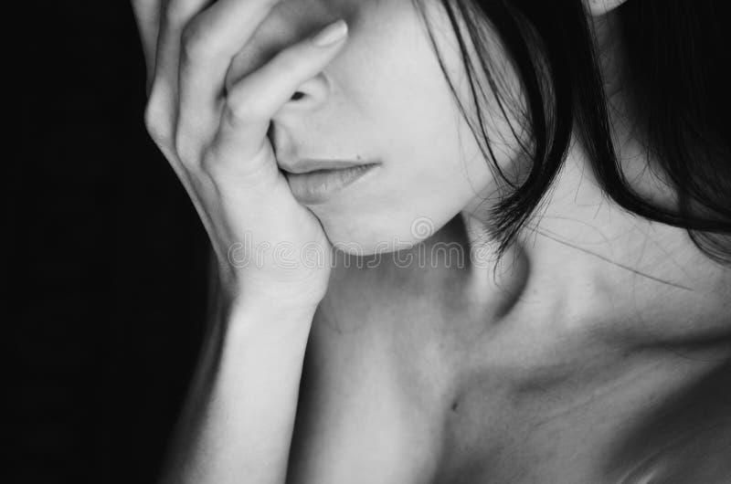 La mujer joven cubre su cara con blanco del negro de la mano fotos de archivo libres de regalías