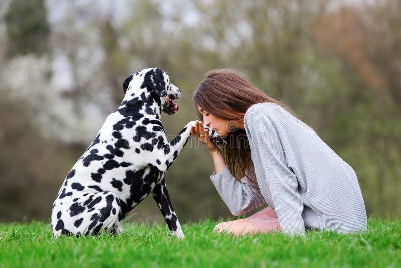 La mujer joven da a su perro dálmata un beso en la pata imagen de archivo