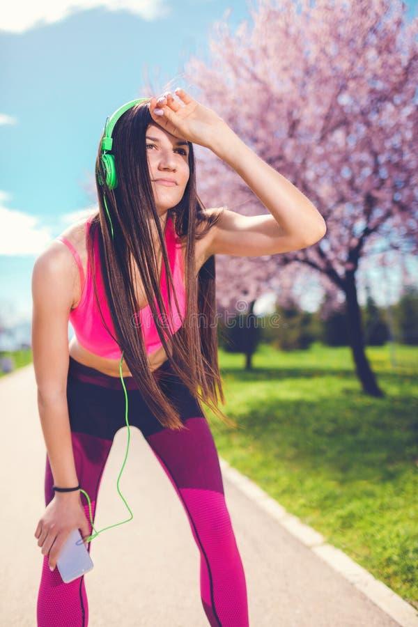 La mujer joven de la aptitud con los auriculares ejercita en el parque imagen de archivo
