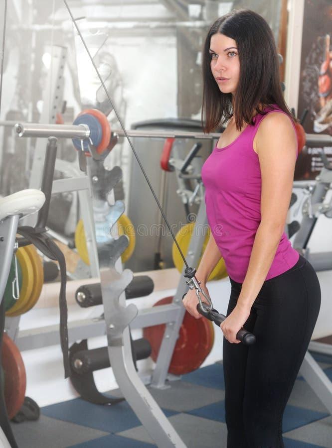 La mujer joven de la aptitud ejecuta ejercicio con la ejercicio-máquina imagenes de archivo
