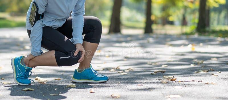 La mujer joven de la aptitud que lleva a cabo su lesión en la pierna de los deportes, muscle doloroso durante el entrenamiento Co imagen de archivo