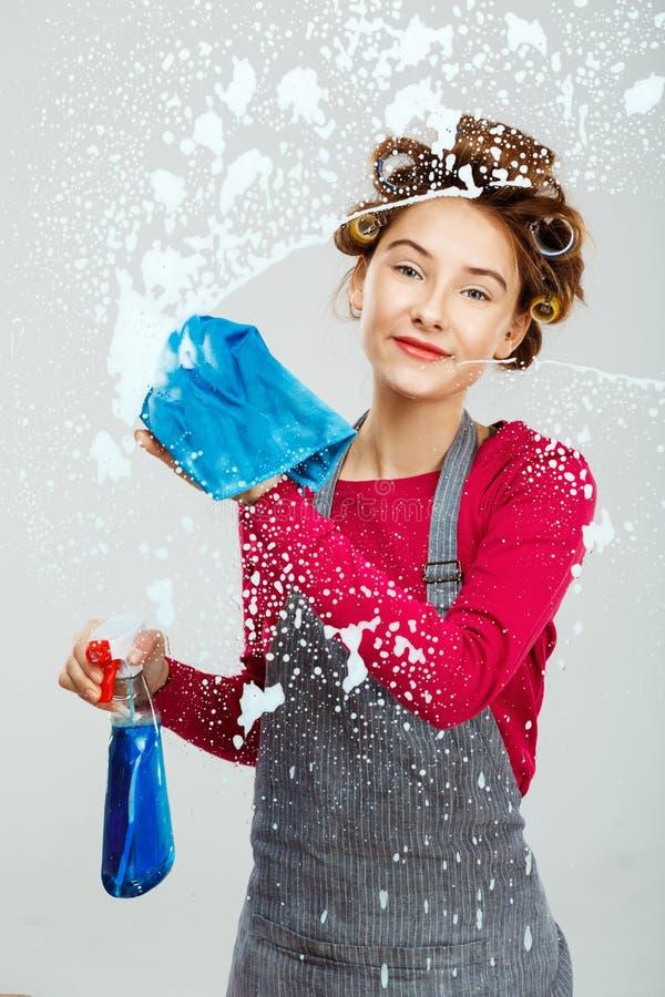 La mujer joven de Charning lava ventanas con la toalla azul fotografía de archivo libre de regalías