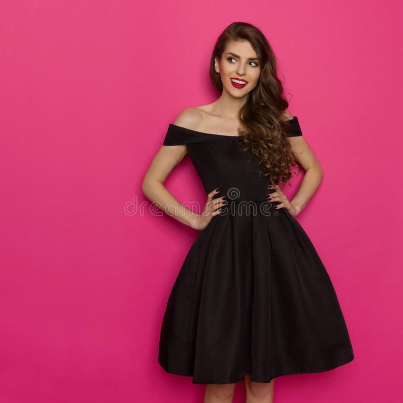 La mujer joven de Elegany en vestido de cóctel negro está mirando lejos imagenes de archivo