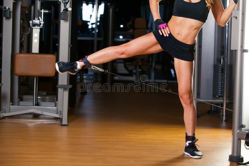 La mujer joven de la aptitud ejecuta ejercicio en cadera con la cruce del cable de la ejercicio-máquina en gimnasio imagen de archivo