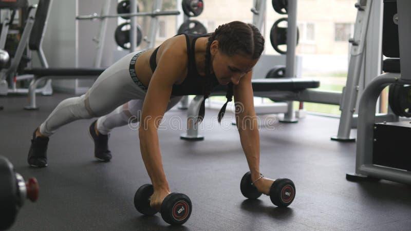 La mujer joven de la aptitud que hace pesa de gimnasia rema en el gimnasio del crossfit Muchacha juguetona que ejercita - peso de fotos de archivo