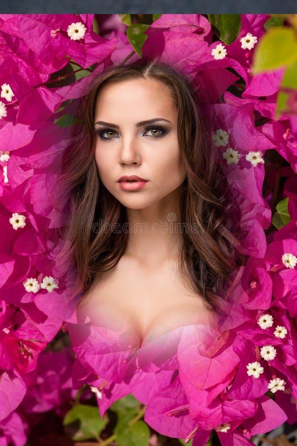 La mujer joven de la belleza con las flores de la buganvilla rosada imagen de archivo