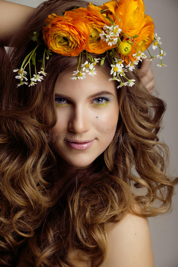La mujer joven de la belleza con las flores y compone fotografía de archivo