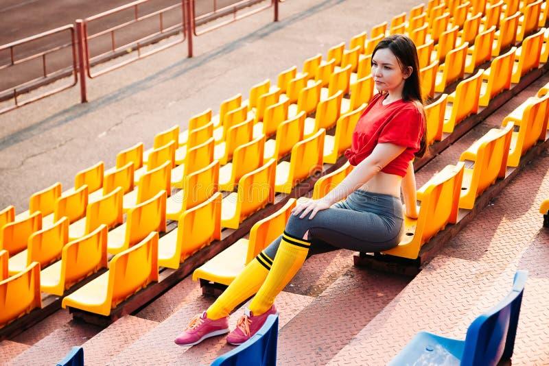 La mujer joven de los deportes en ropa de deportes en tribuna del estadio se sienta en banco imagen de archivo libre de regalías
