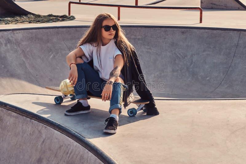La mujer joven de moda con el pelo y las gafas de sol largos se est? sentando en el skatepark fotos de archivo