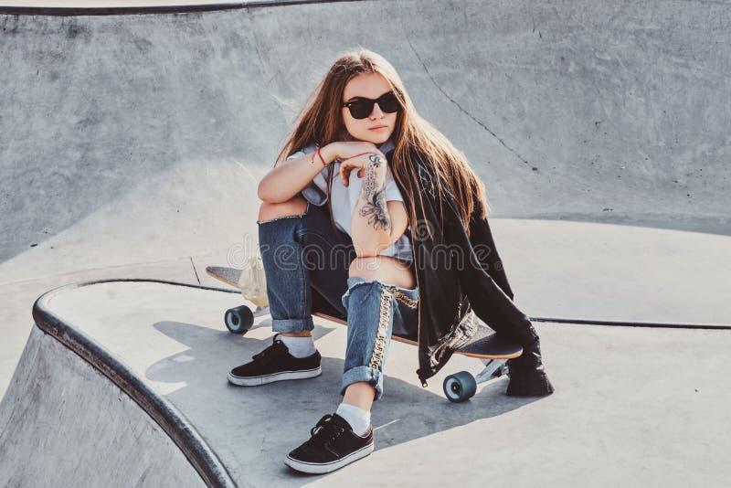 La mujer joven de moda con el pelo y las gafas de sol largos se est? sentando en el skatepark imagenes de archivo