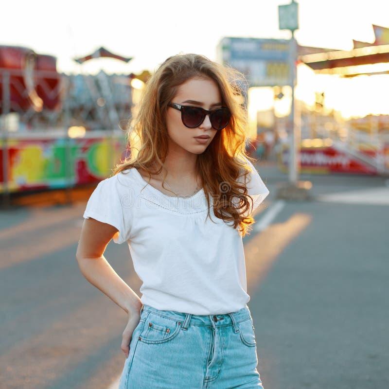 La mujer joven de moda del inconformista del pelirrojo en una camiseta blanca en gafas de sol elegantes en vaqueros azules del vi imagenes de archivo