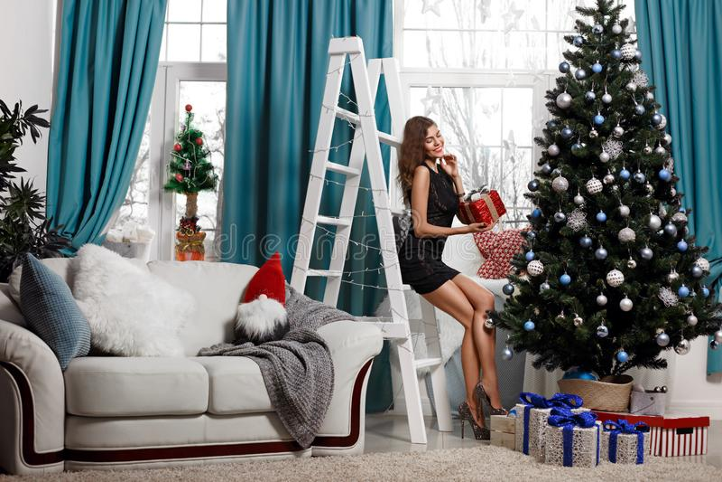 La mujer joven de moda en vestido festivo presenta los regalos debajo del árbol de navidad en la sala de estar, disfrutando de la fotos de archivo libres de regalías