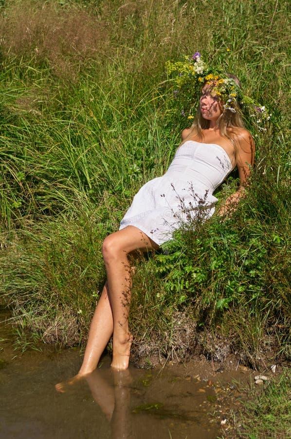 La mujer joven de la muchacha bonita con el pelo largo rubio natural y la cara hermosa en la guirnalda blanca del vestido y de la imagen de archivo libre de regalías