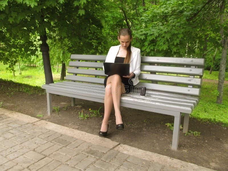 La mujer joven de pelo largo rubia en ropa de la oficina se sienta en un banco en el parque con un ordenador portátil y un café E imagen de archivo libre de regalías