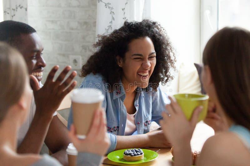 La mujer joven de la raza mixta que ríe en mejores amigos bromea imagen de archivo