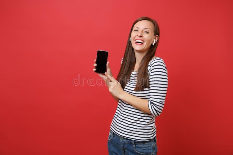 La mujer joven de risa con los auriculares inalámbricos sostiene el teléfono móvil con música que escucha de la pantalla vacía ne imagen de archivo