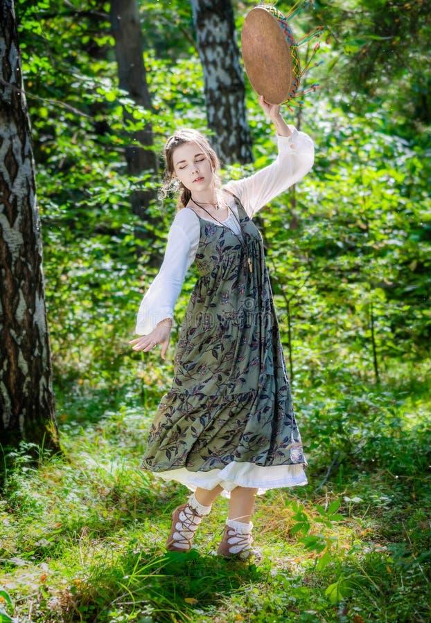 La mujer joven de una bruja realiza una danza ritual foto de archivo