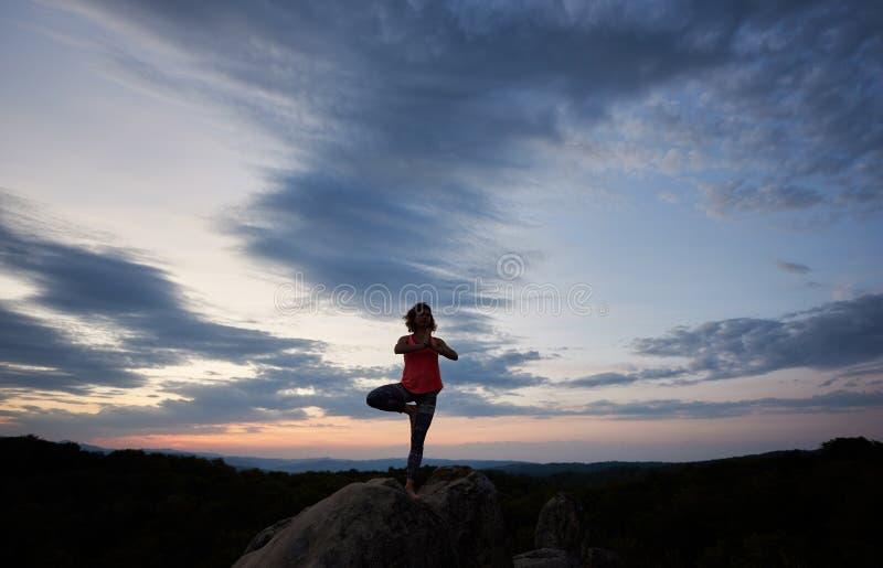 La mujer joven del ajustado que hace yoga ejercita la situación descalzo en una pierna en roca grande de la montaña foto de archivo libre de regalías