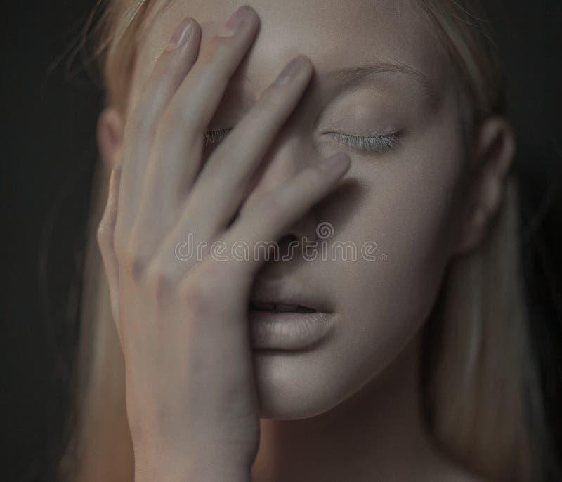 La mujer joven del albino con los ojos cerrados toca su cara fotografía de archivo