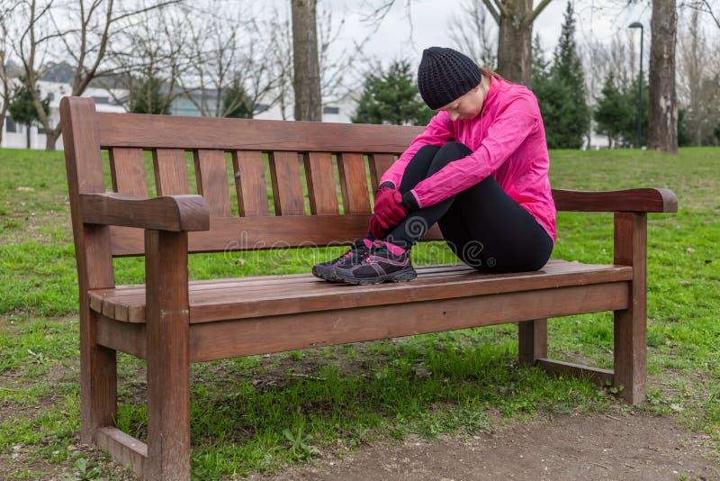La mujer joven del atleta cansó o presionó la reclinación sobre un banco imagen de archivo libre de regalías