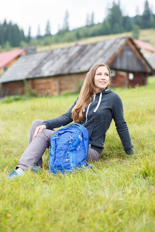La mujer joven del backpacker se sienta en hierba en montañas fotos de archivo libres de regalías