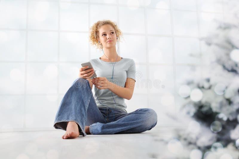 La mujer joven del concepto de la Feliz Navidad escucha las canciones de la Navidad de su teléfono móvil con los teléfonos del oí fotografía de archivo