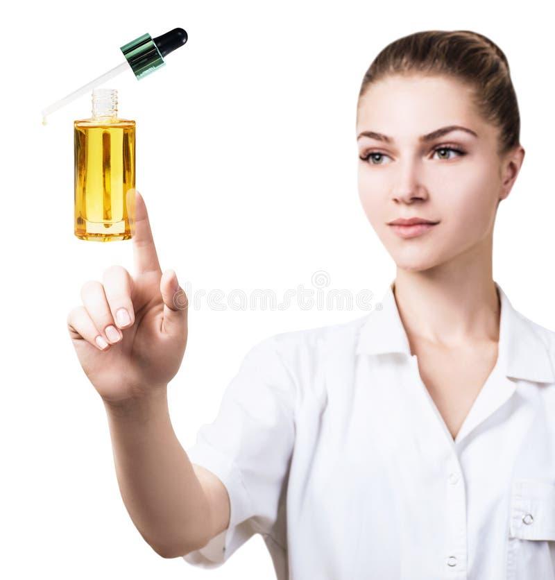 La mujer joven del cosmetologist presenta el aceite de los cosméticos imagen de archivo