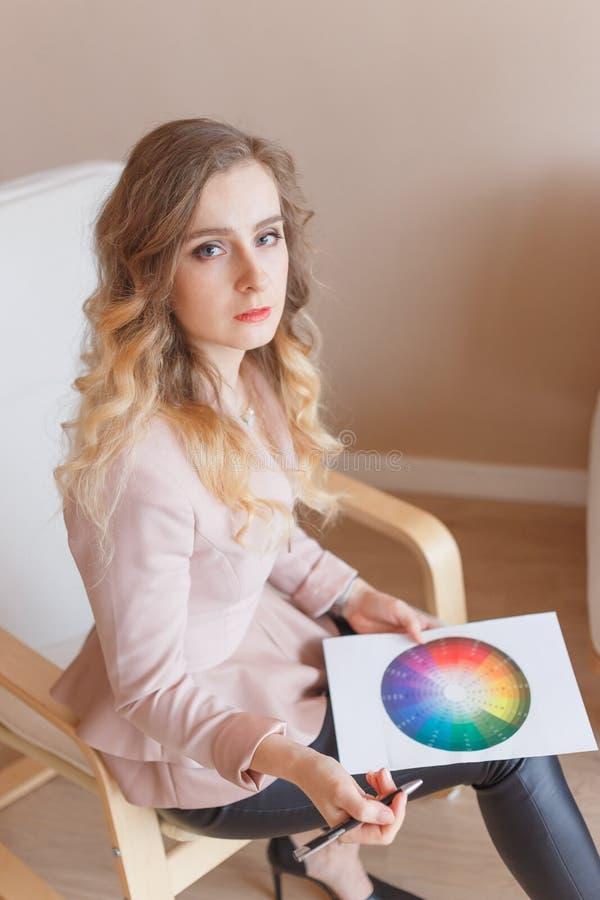 La mujer joven del diseñador de ropa utiliza un círculo de color gráfico imagen de archivo
