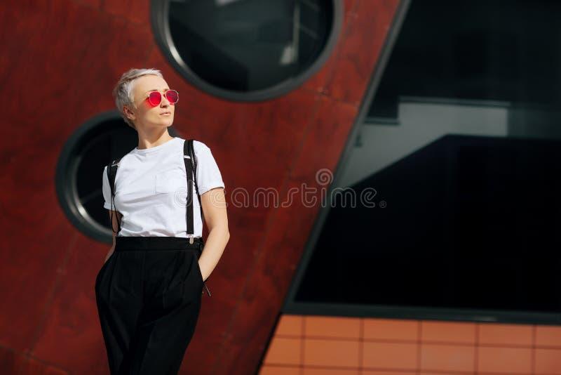 La mujer joven del inconformista bastante de moda con las gafas de sol rojas elegantes permanece la pared cercana una mirada lejo fotos de archivo libres de regalías