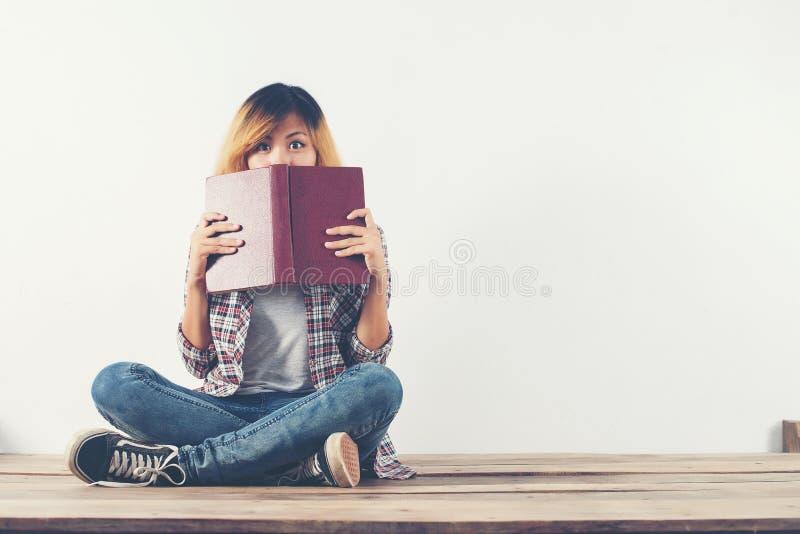 La mujer joven del inconformista tomó el libro de su cara con la timidez, whe foto de archivo