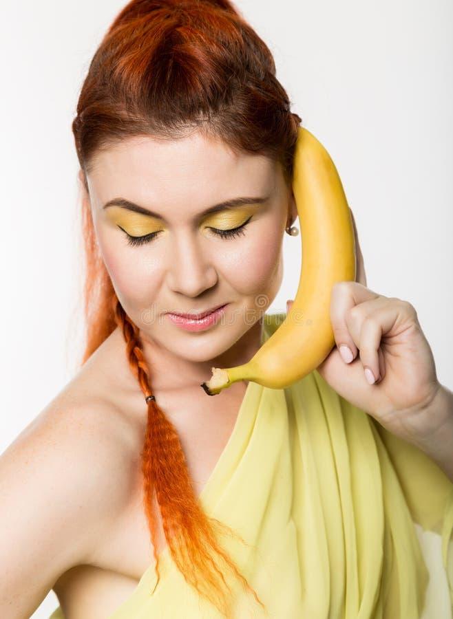 La mujer joven del pelirrojo que sostiene el plátano cerca de su cara le gusta smartphone en un fondo blanco imágenes de archivo libres de regalías