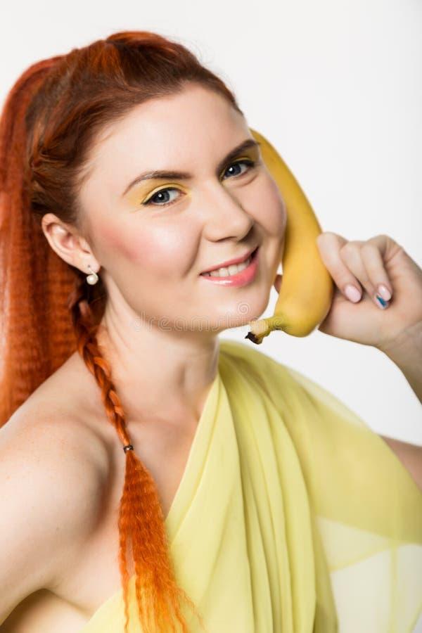 La mujer joven del pelirrojo que sostiene el plátano cerca de su cara le gusta smartphone en un fondo blanco imagenes de archivo