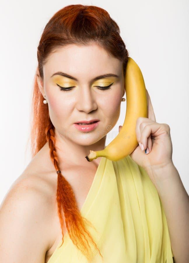La mujer joven del pelirrojo que sostiene el plátano cerca de su cara le gusta smartphone en un fondo blanco imagen de archivo