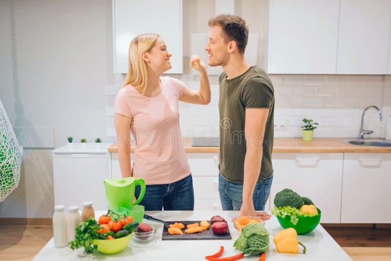 La mujer joven del vegano da cortar el pedazo de vegetal su marido por mañana Familia de amor que cocina verduras orgánicas adent imagen de archivo libre de regalías