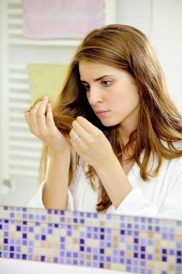 La mujer joven delante del espejo se preocupó del pelo dañado foto de archivo libre de regalías