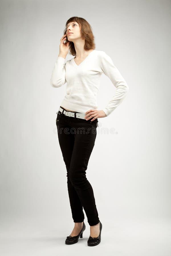 La mujer joven delgada que habla en el teléfono celular imagen de archivo