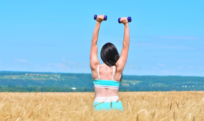 La mujer joven deportiva coge las manos con pesas de gimnasia al aire libre fotos de archivo libres de regalías
